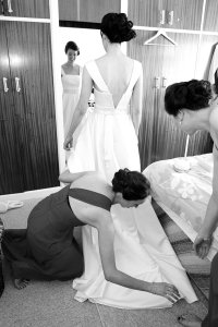 Bride having her wedding dress fixed by bridesmaids.