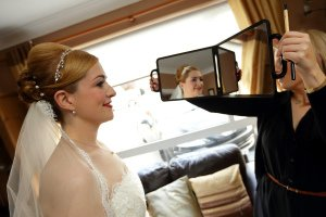 Bride checking her makeup on morning of the wedding.
