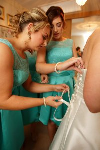 Bridal dress being buttoned up by bridesmaids.