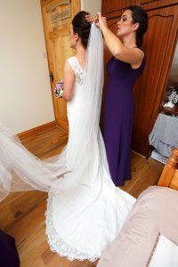 Bride having veil put on by bridesmaid.
