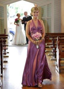 Bridesmaid comign down aisle in church.