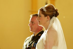Military wedding ceremony, couple focusing on sermon.