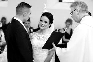 Taking their wedding vows.