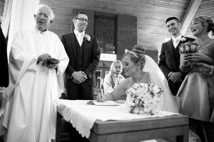 Bride signing the register.