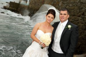 Bride & Groom by stormy sea, with veil flying in the wind.