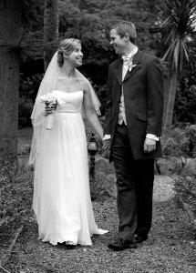 Bride and Groom walking in trees.