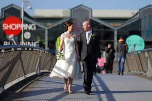 Bride and Groom walking across bridge in Dublin.