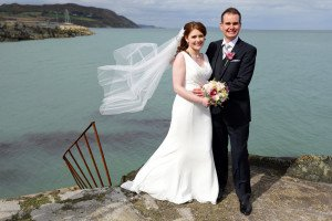 Bride & Groom by the sea, dramatic photo.