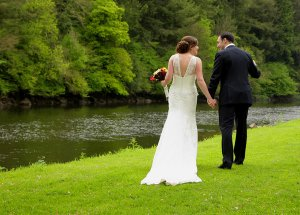 Bride and Groom walking hand in hand at river bank.