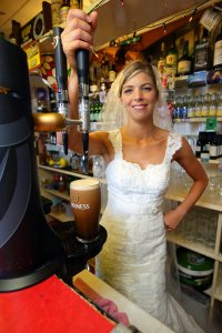 Bride pulling a pint of Guinness.