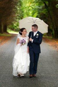 Bride and Groom walking with umbrella, Ireland.