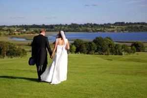 Bride and Groom wedding photo walking by lake.