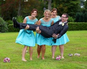 Bridesmaids lifting Groom, fun wedding photo.