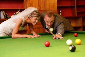 Bride and Groom playing pool at their wedding reception, fun photo.