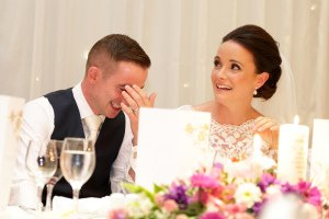 Wedding speeches, bride and groom laughing.