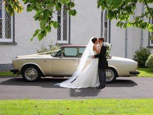 Bride and Groom kissing at car.